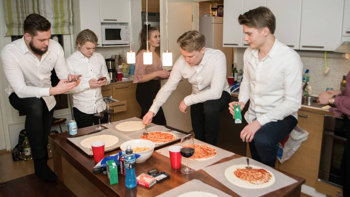 Neljä miestä tekee pizzaa kotona uuden vuoden aattona