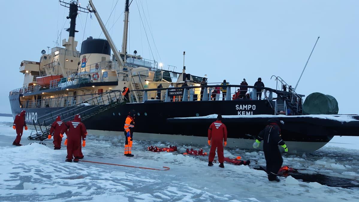 Jäänmurtaja Sampo pysähdyksissä Perämerellä kun turistit kelluvat meressä.