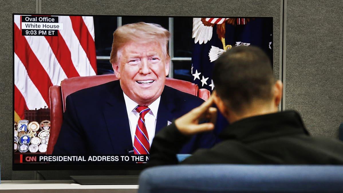 Mies katselee televisiosta presidentti Trumpin puhetta.