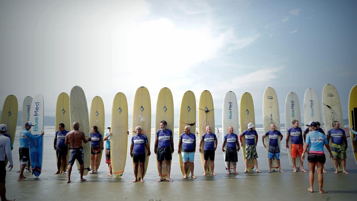 Iäkkäitä ihmisiä rivissä surffilautojen kanssa.