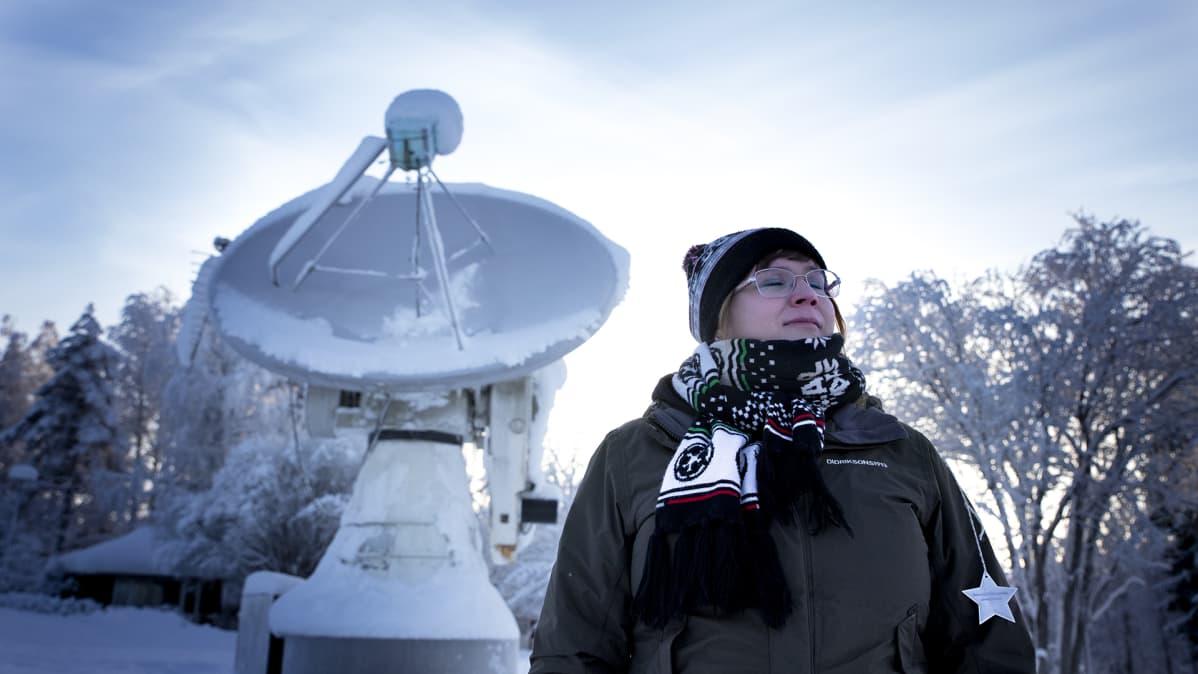 Päivikki Puolakka seisoo radioteleskoopin edessä silmät kiinni.