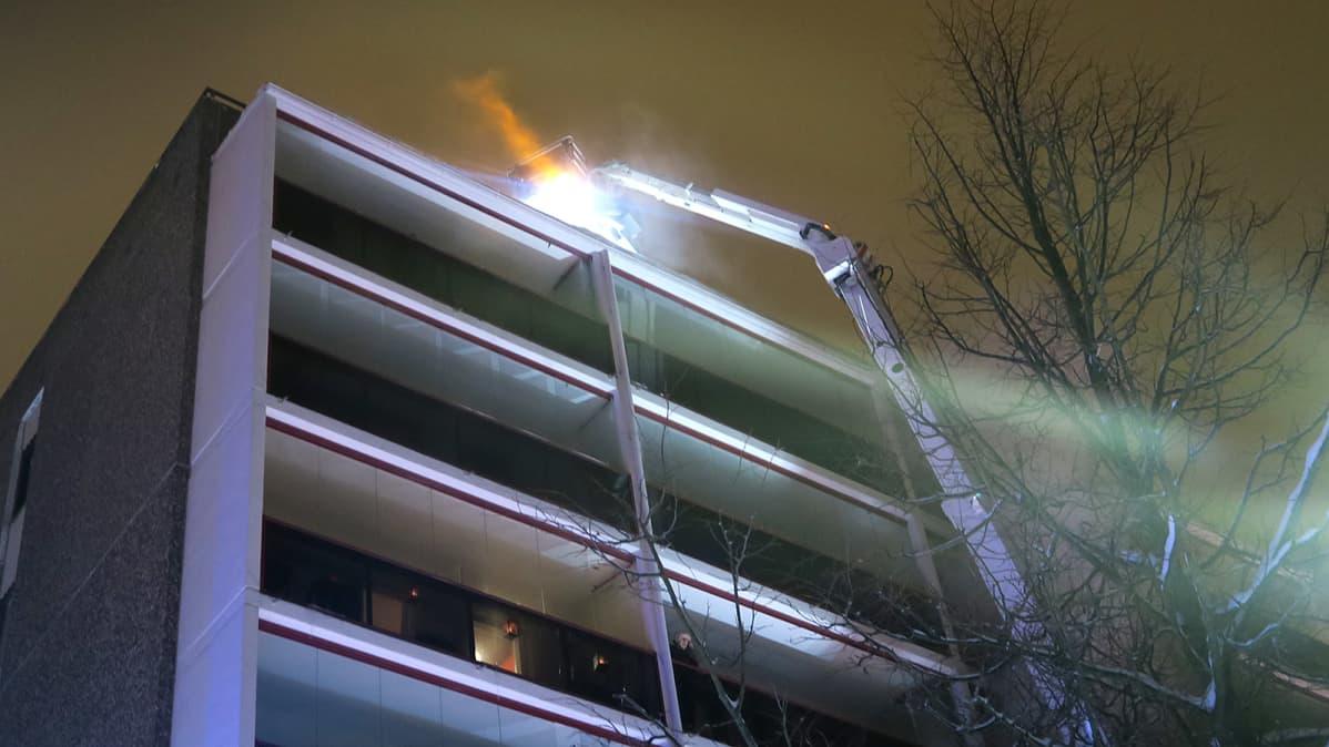 Nosturi kurottaa kerrostalon katolle talviyössä