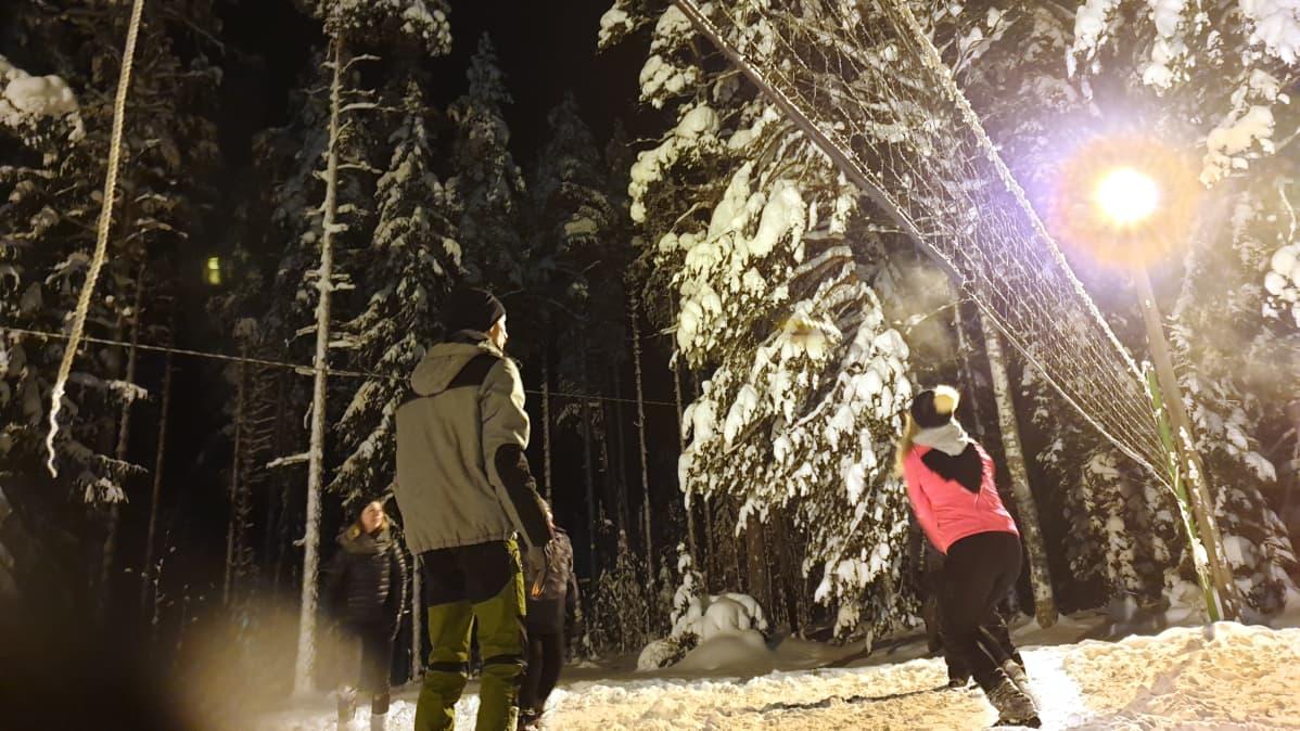 Ihmisiä pelaamassa lentopalloa talvella.