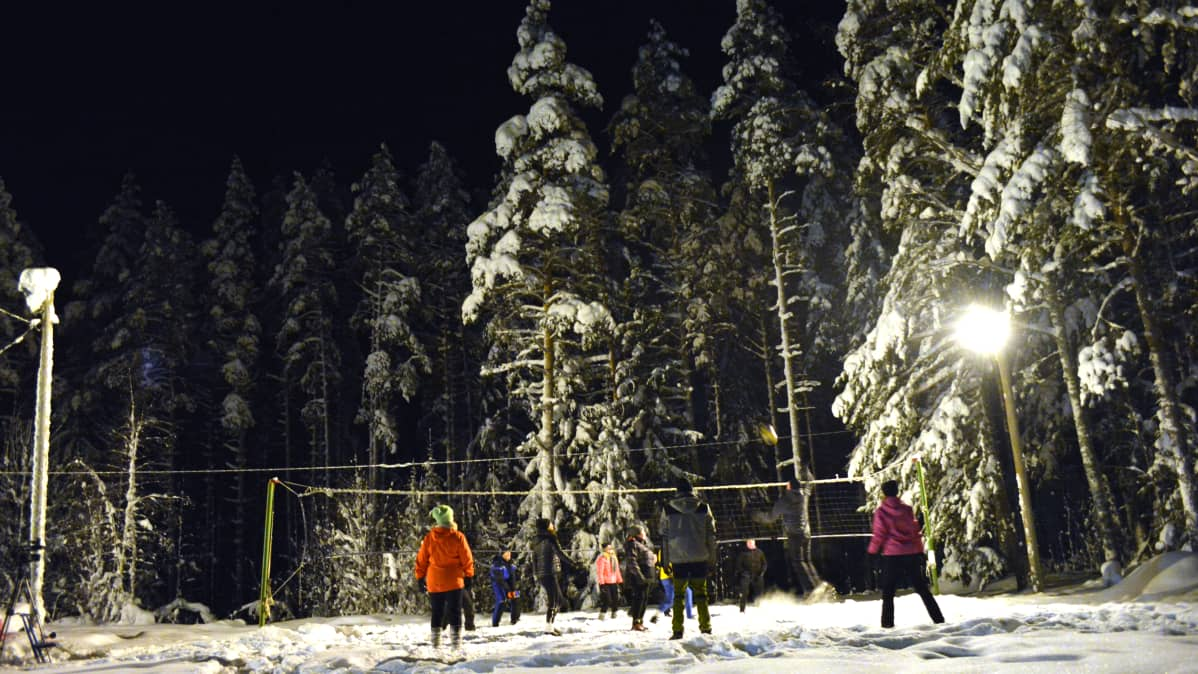 Ihmiset pelaamassa lentopalloa talvella ulkona.