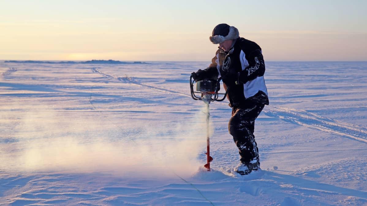 Tauno Suomalainen kairaa reikää jäähän