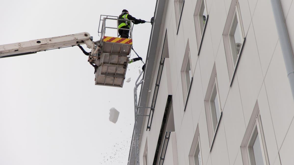 Työmiehet pudottavat lumia kerrostalon katolta
