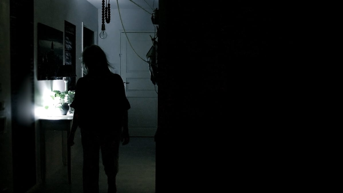 Nainen kävelee pimeässä asunnossa yöllä.