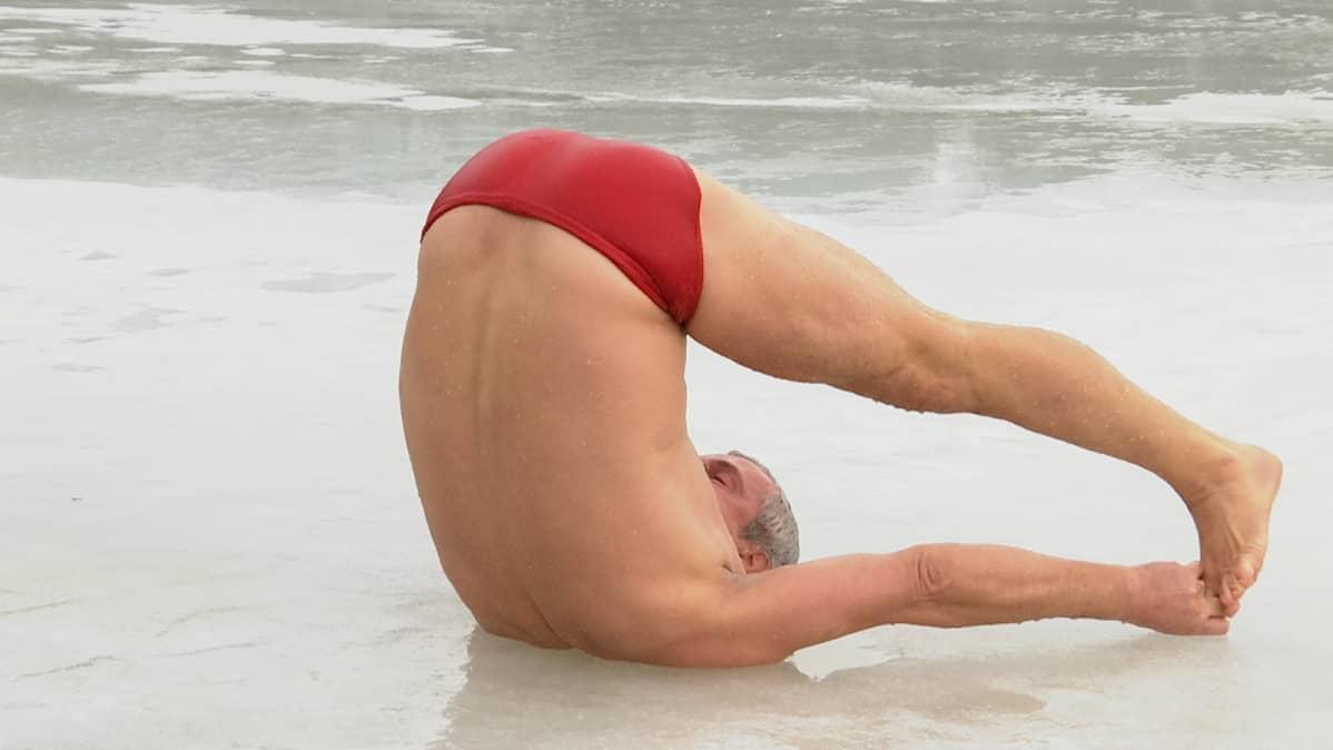 Joogaohjaaja Magnus Appelberg tekee supta konasanan (selinmakuulla suorat jalat ja suorilla käsillä varpaista kiinni) vetisellä jäällä.