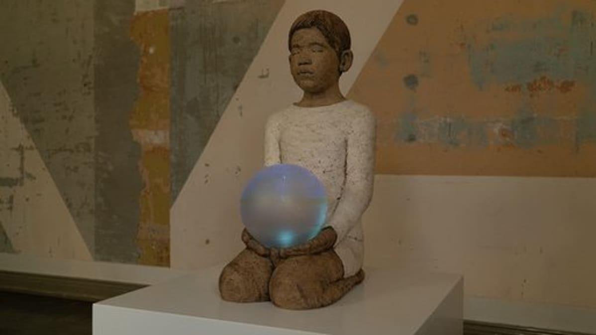 Keramiikkaveistos, jossa lapsi pallo  käsissään.