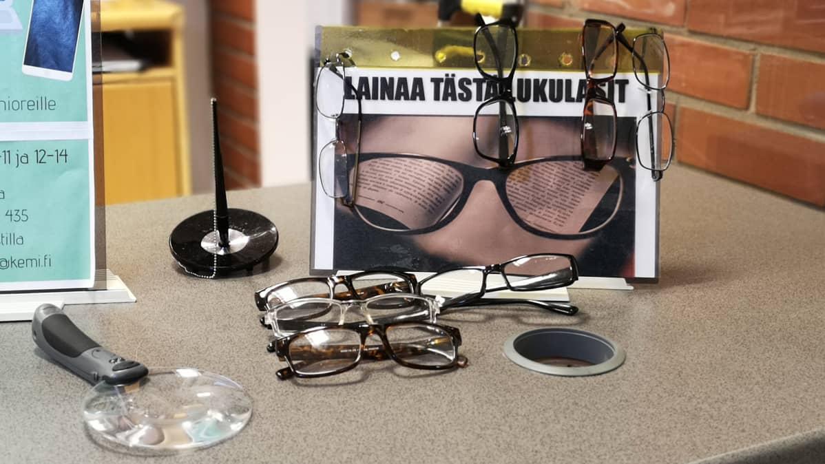Suurennuslasi ja silmälaseja pöydällä.