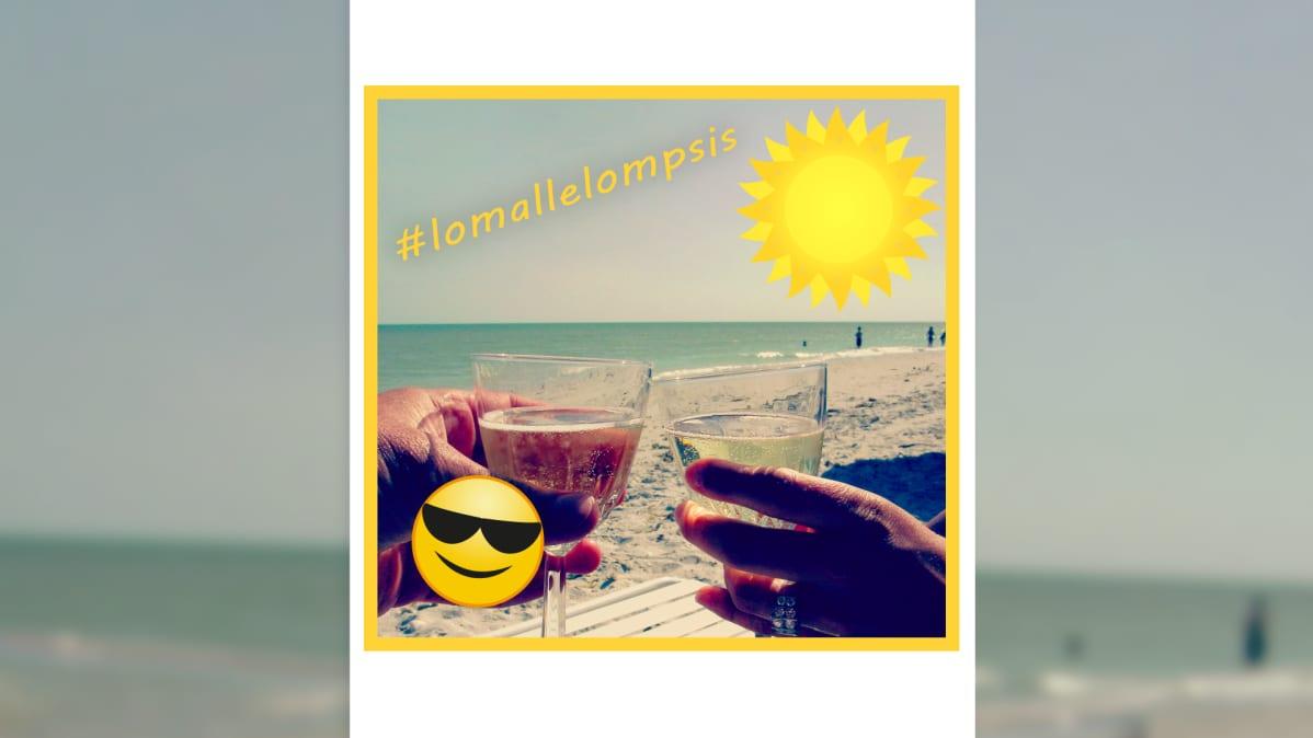 Kaksi viinilasia skoolaa uimarannalla. Teksti #lomallelompsis, auringon kuva, aurinkolasinen emojinaama