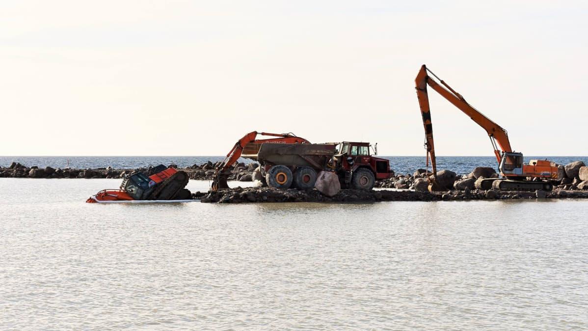 Kaivuri vajonneena puoliksi mereen aallonmurtajalta Kaunissaaren satamassa Pyhtäällä.