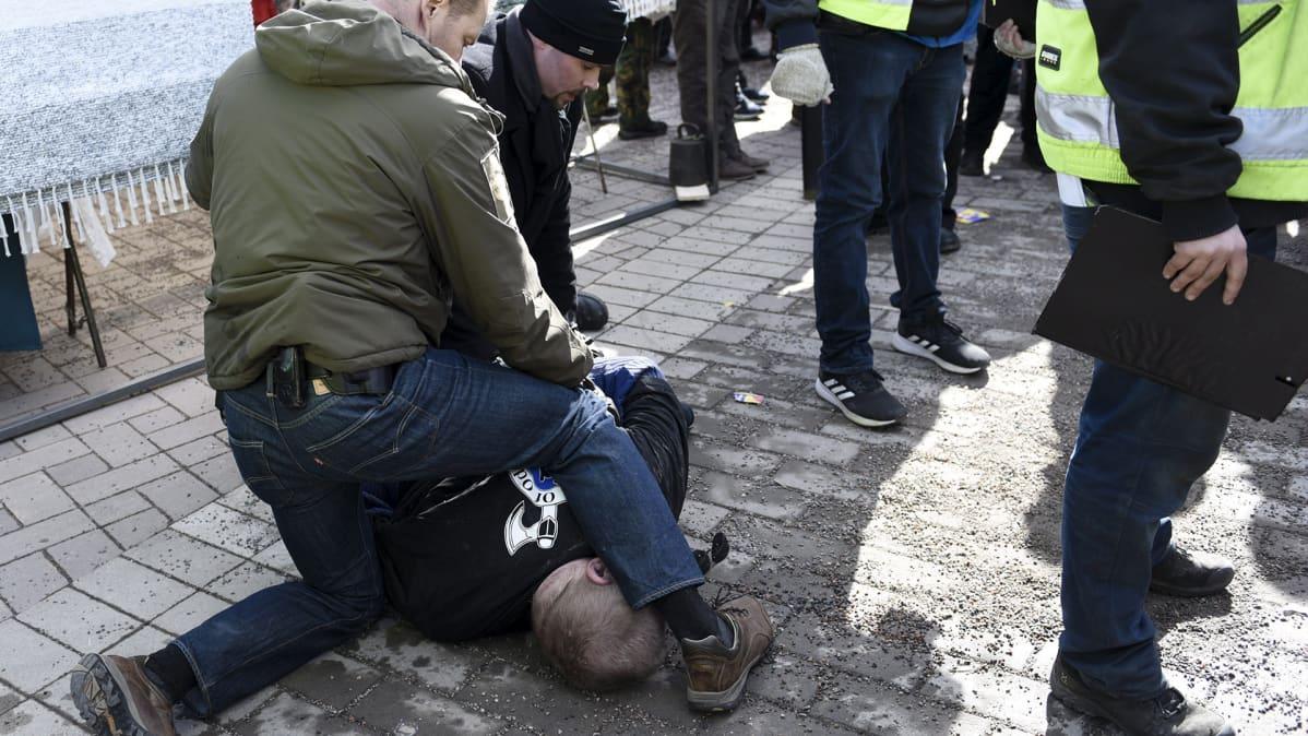 Soldiers of Odin -takkinen mies, joka yritti lyödä sinisten Timo Soinia, maahan kaadettuna ja kiinni otettuna Korson maalaismarkkinoilla Vantaalla sunnuntaina 24. maaliskuuta.