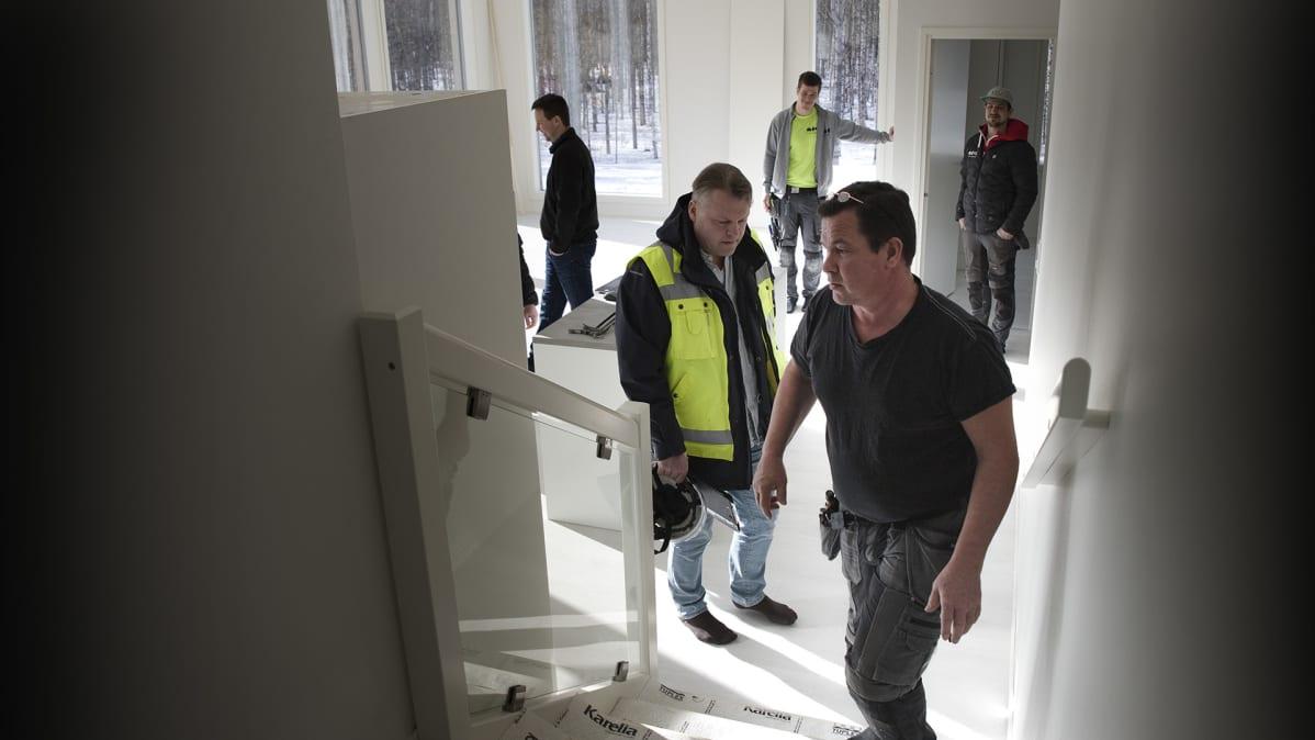 Rakennusinsinööri Tuomo Rauhala  ja lupa-arkkitehti Jouko Koskinen tarkastavat uutta omakotitaloa Jyväskylässä.
