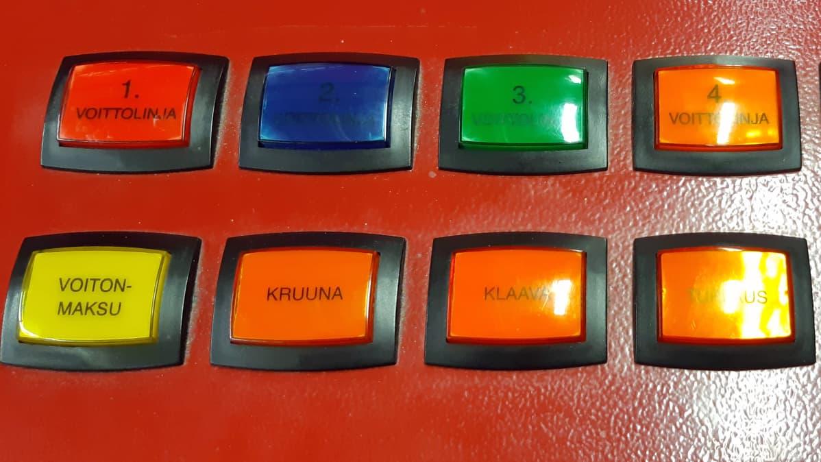 Rahapeliautomaatin värikkäitä nappuloita rivissä.