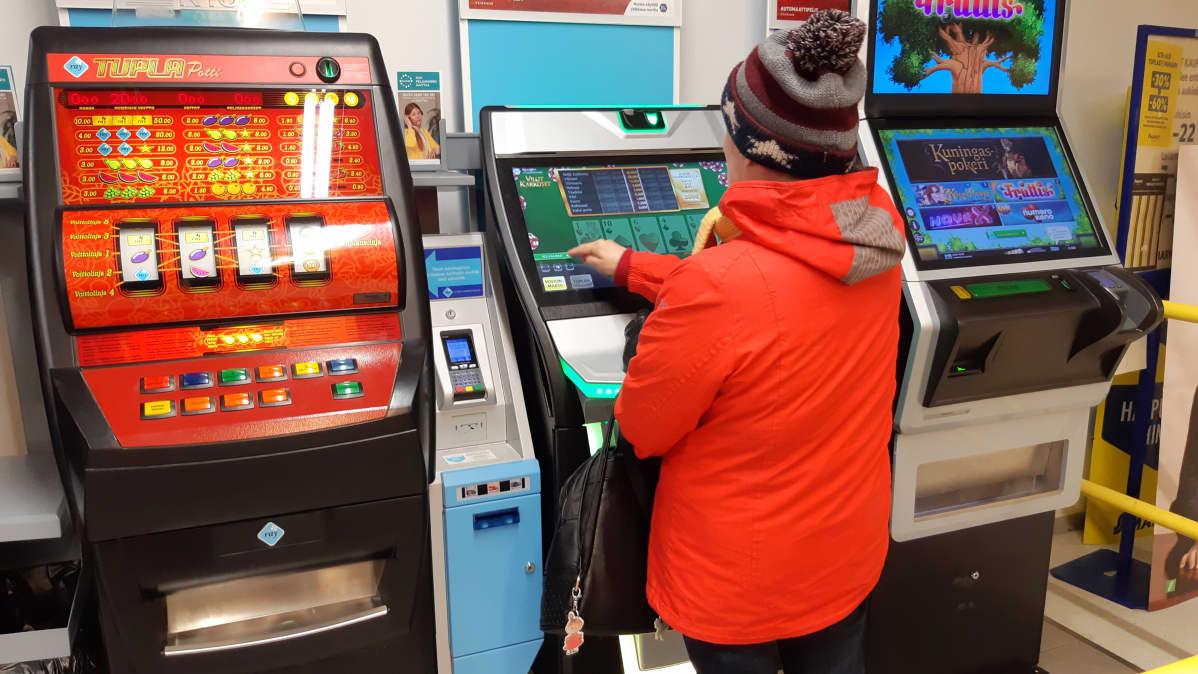 Punatakkinen nainen pelaa rahapeliautomaattia  kaupassa.