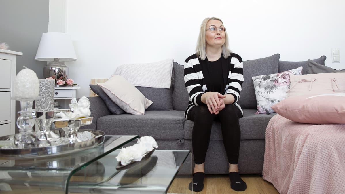 Nainen istuu sohvalla.