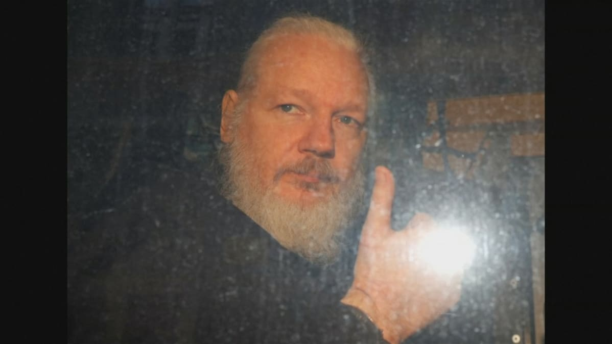 Kuvassa Julian Assange poliisiauton kyydissä. Hän näyttää oikealla kädellään peukaloa.