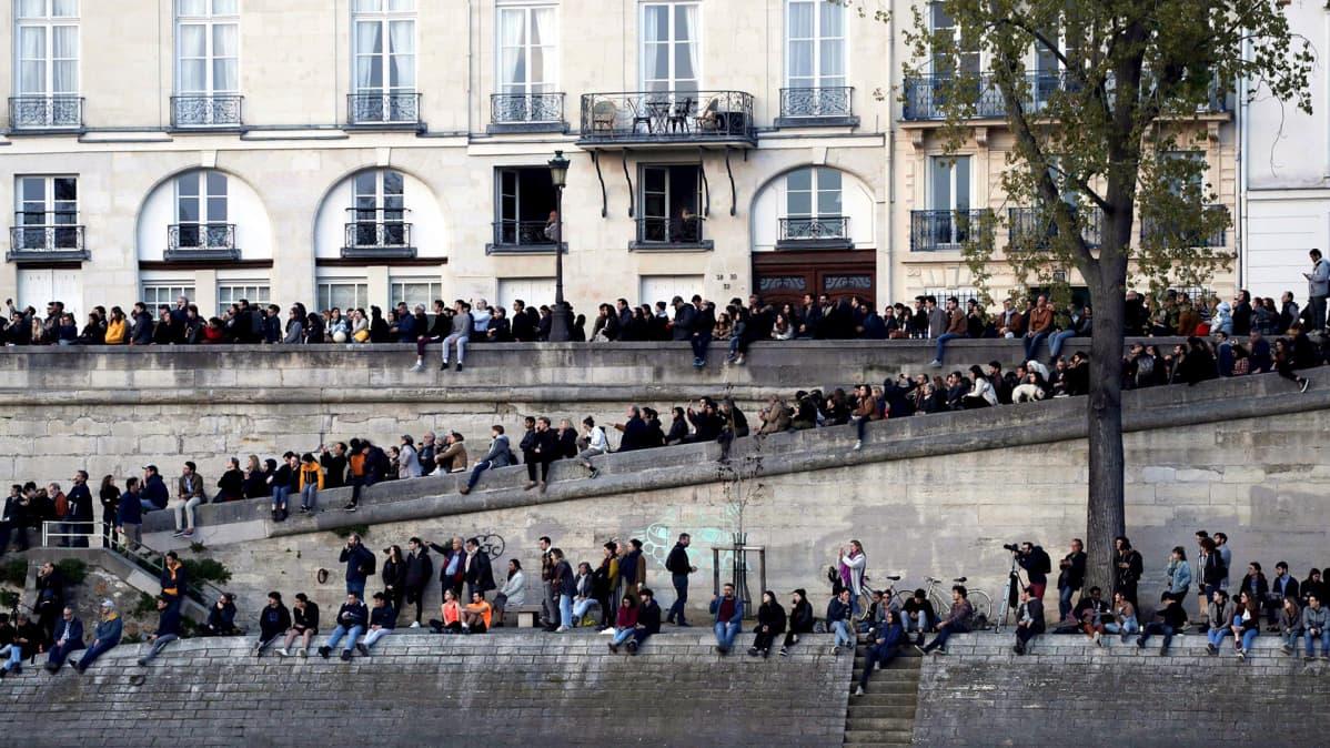 Ihmiset seurasivat Notre Damen katon sammutustöitä Seinen toiselta rannalta 15. huhtikuuta.
