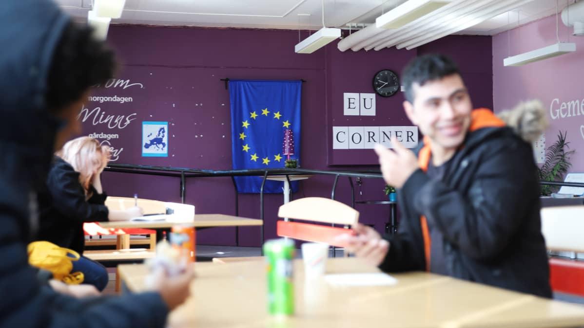 Lukiolaisia Haaparannan Tornedalsskolanin kahvilassa, taustalla EU Corner.