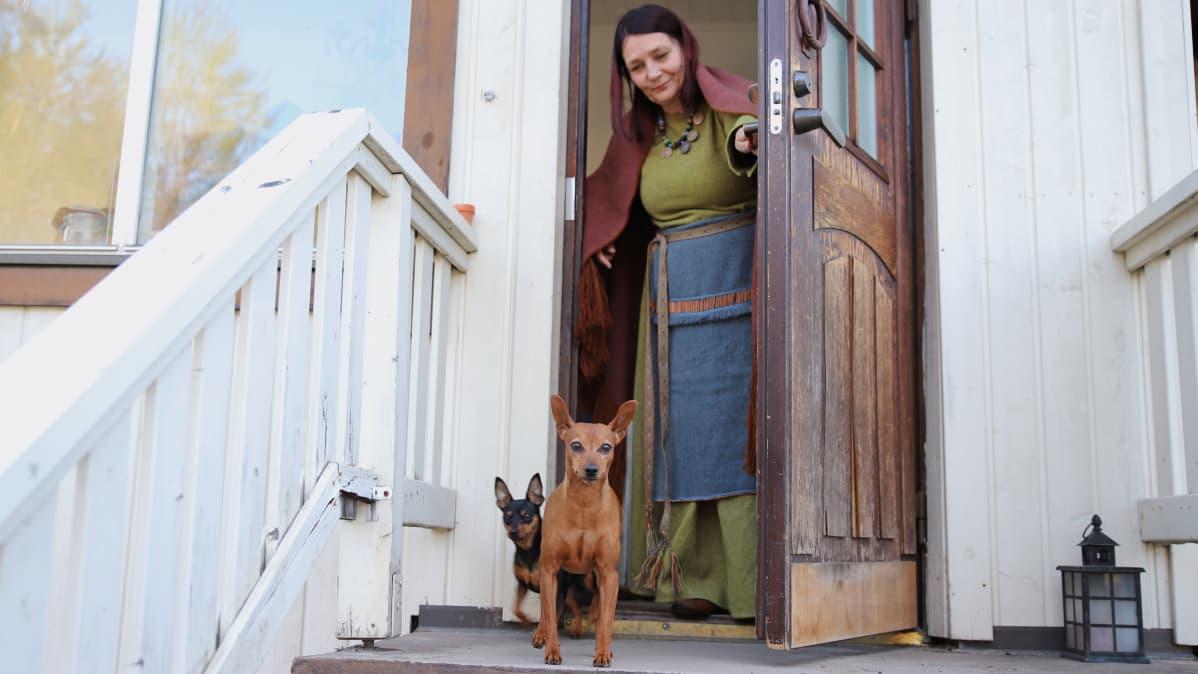 Mervi Pasanen kotiovellaan muinaispuku päällä. Etualalla kaksi koiraa.