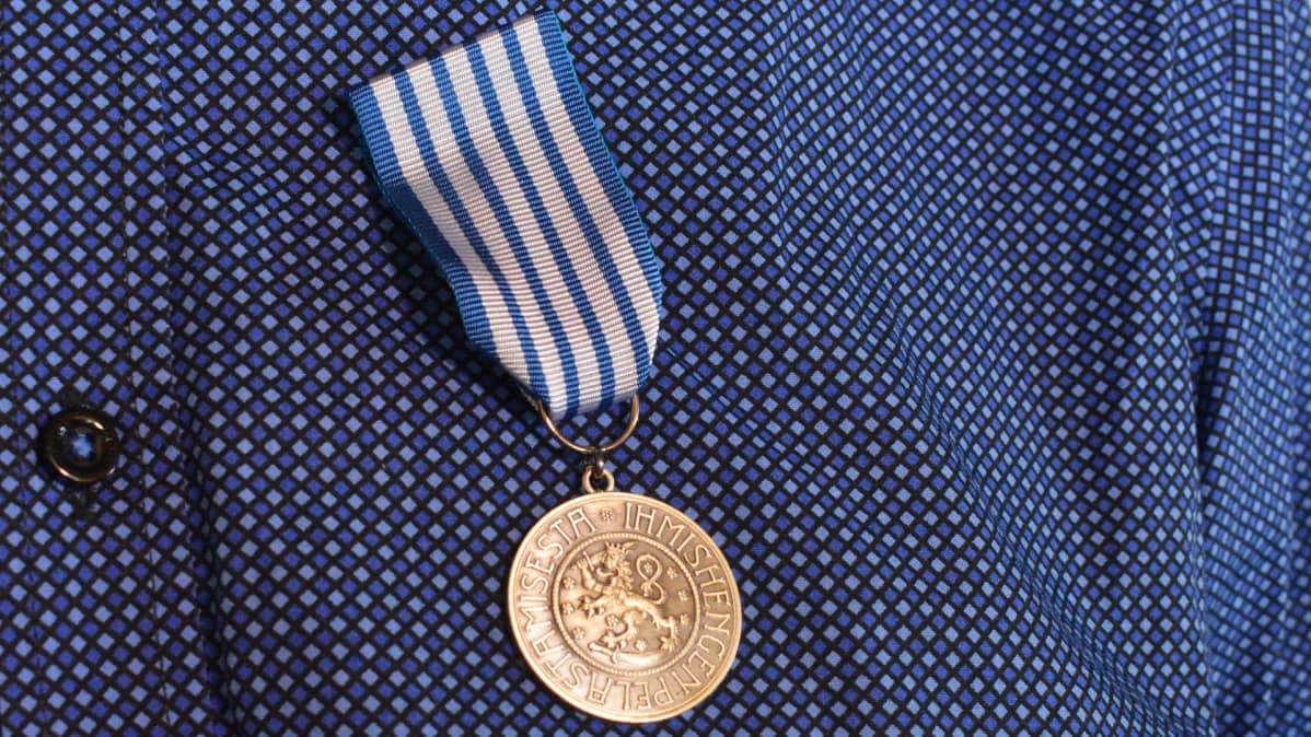 Ihmishengen pelastamisesta annettu mitali koristaa Tauno Vuorisalon rintapieltä.