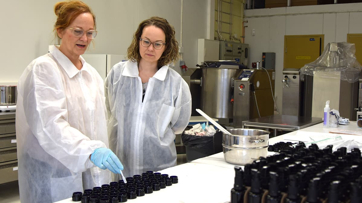 Kaksi naista tarkastelee poskiväriä luonnonkosmetiikkayrityksen tuotantotiloissa
