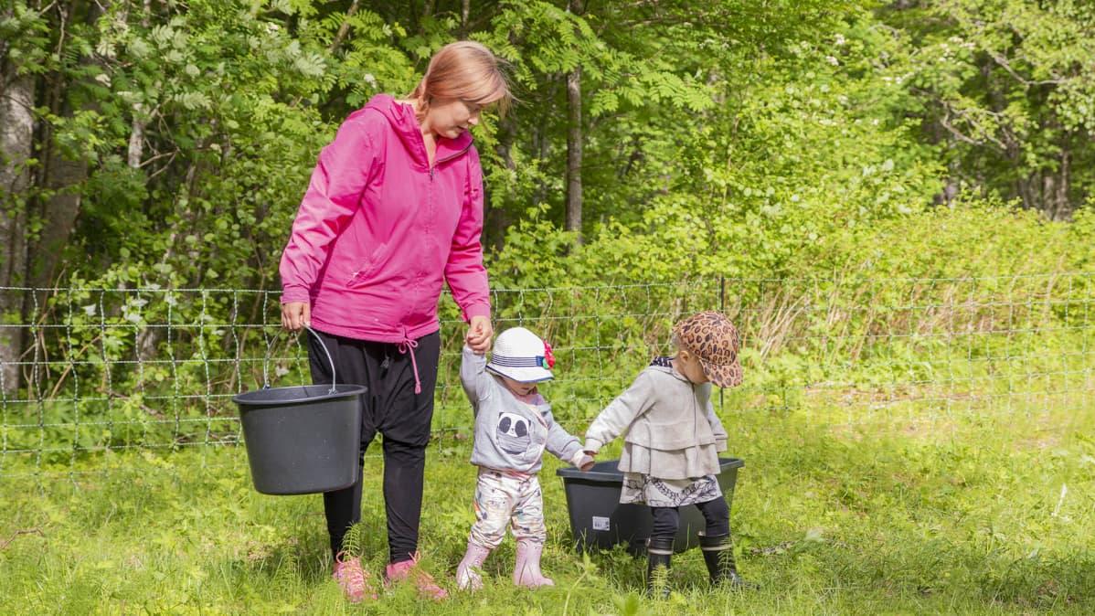 Anni Matero lapsien kanssa hakemassa vettä.