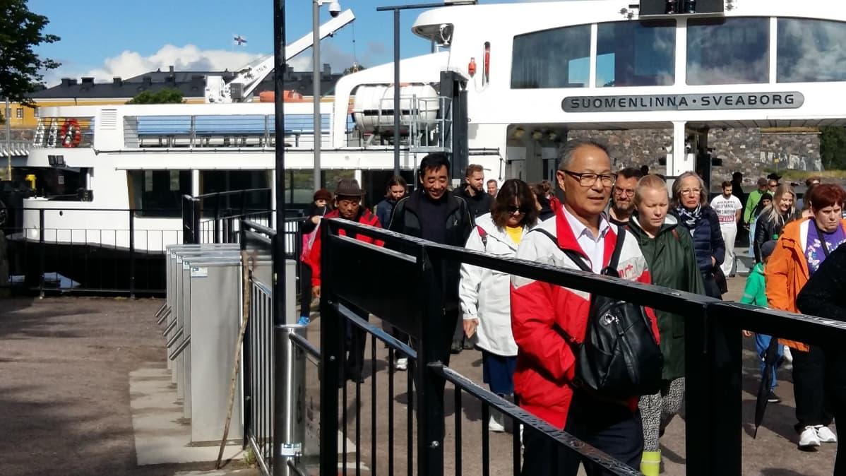 Lautta on saapunut Suomenlinnaan. Lautasta astuu maihin matkailijoita ja paikallisia asukkaita.