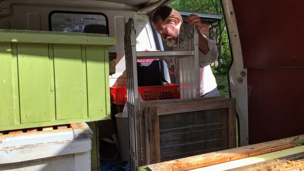 Hannu Luukinen pakkaa pakettiautoaan mehiläisparven kiinniottokeikalle.