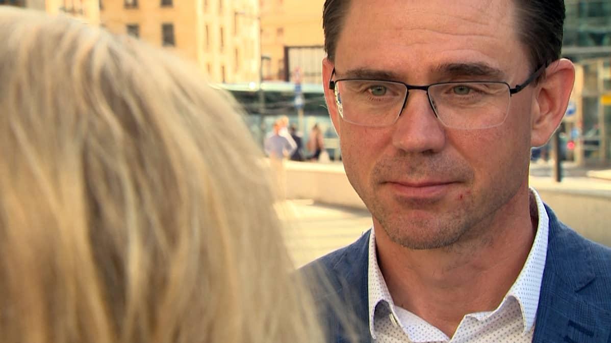 Jyrki Katainen keskustelee toimittajan kanssa kadulla.