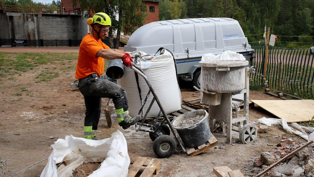 työmies kuljettaa laastipaljua nokkakärryillä