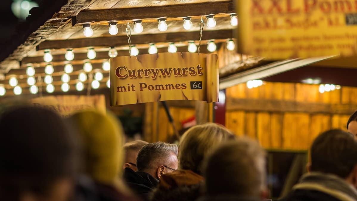 Mainoskyltissä myytiin 'Currywurstia ranskalaisten kera' joulumarkkinoilla Saksassa.