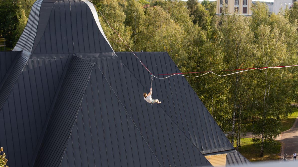 Slackline-harrastajia Lappeen Marian kirkon ja Osuuspankin kattojen väliin viritetyllä liinalla.
