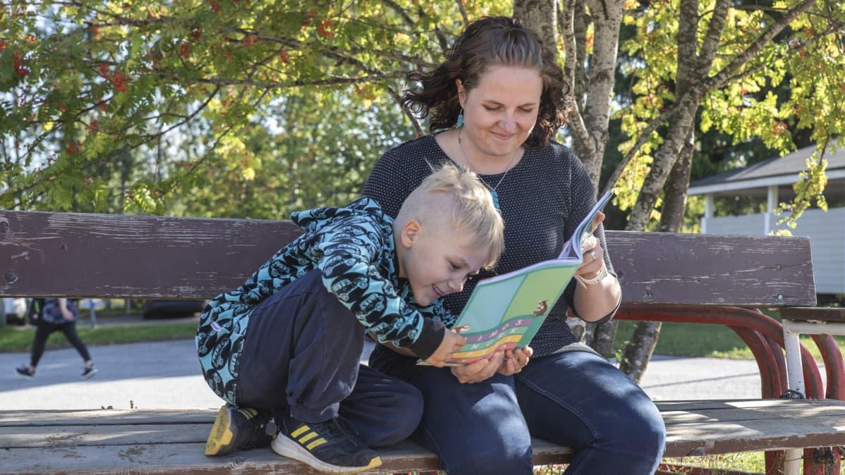 Äiti ja poika katselevat kirjaa ulkona penkillä.