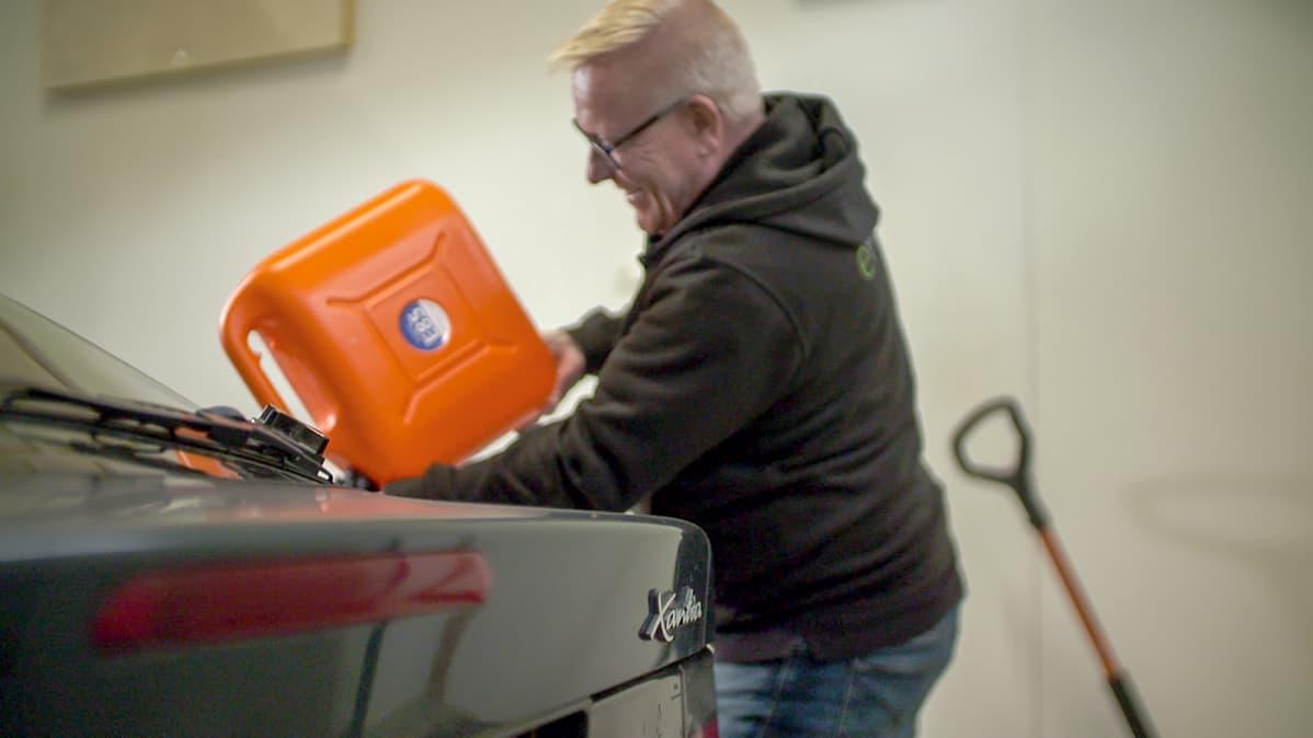 Vesa Vaine (eFlexFuelin Suomen myyntijohtaja) tankkaa oranssista kanisterista RE-85-polttoainetta vihreään Citroen Xantiaan eFlexFuel-asennuspisteessä Pirkkalassa.