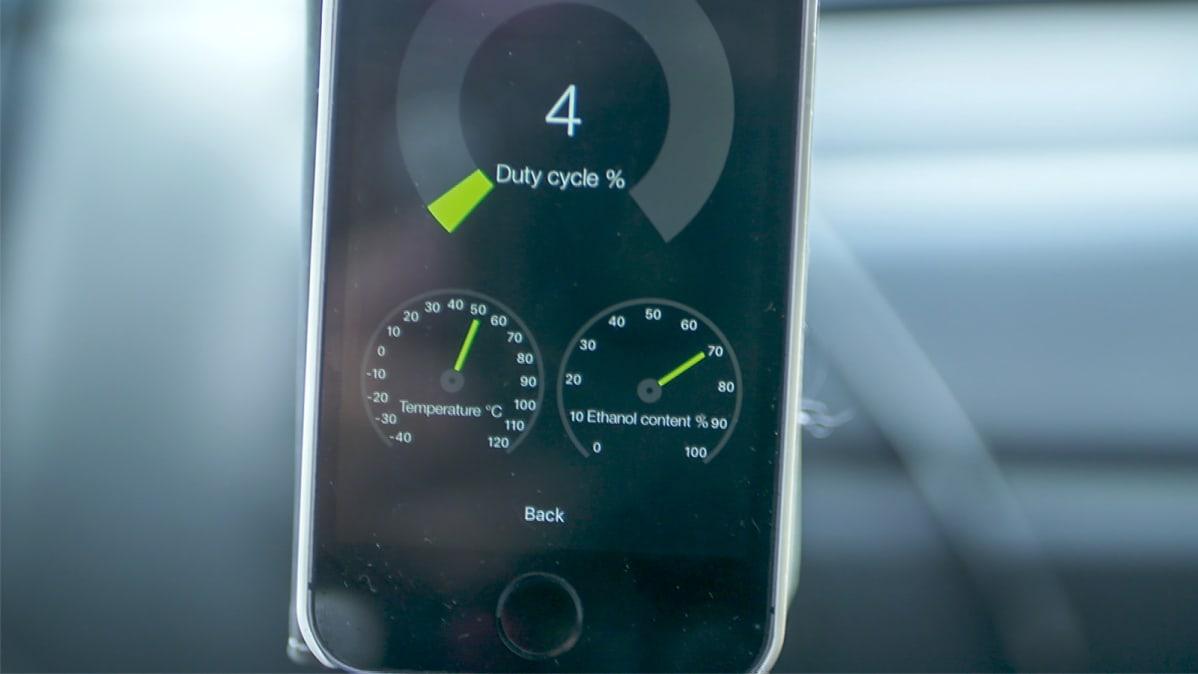 Lähikuva iPhonen näytöstä, jolla pyörii eFlexFuel-etanolimuutossarjan applikaatio. Näyttää ruiskutussuuttimien käyttöasteen, polttoaineen lämpötilan ja polttoaineen etanolipitoisuuden.