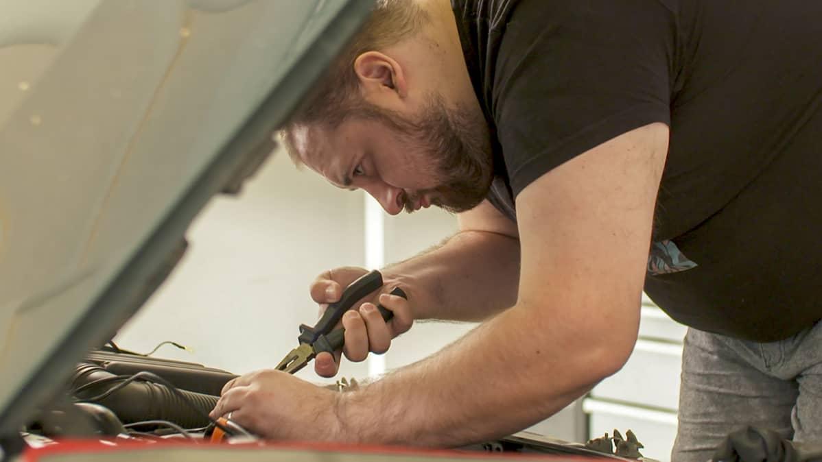 Serko Nieminen (eFlexFuel / StepOne Tech Oy) asentaa pihdit kädessä etanolimuutossarjaa Citroen Xantiaan Pirkkalan asennushallissa.