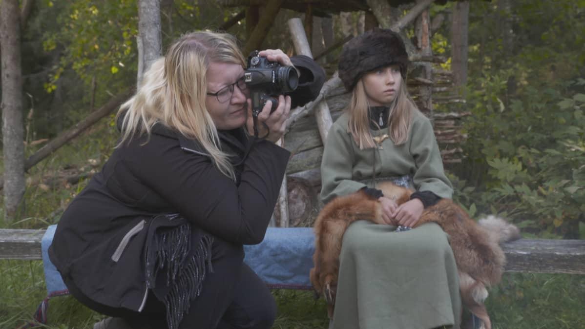 Arkeologi Ulla Moilanen ottaa valokuvaa. takana rautakautisiin pukuihin pukeutuneita ihmisiä