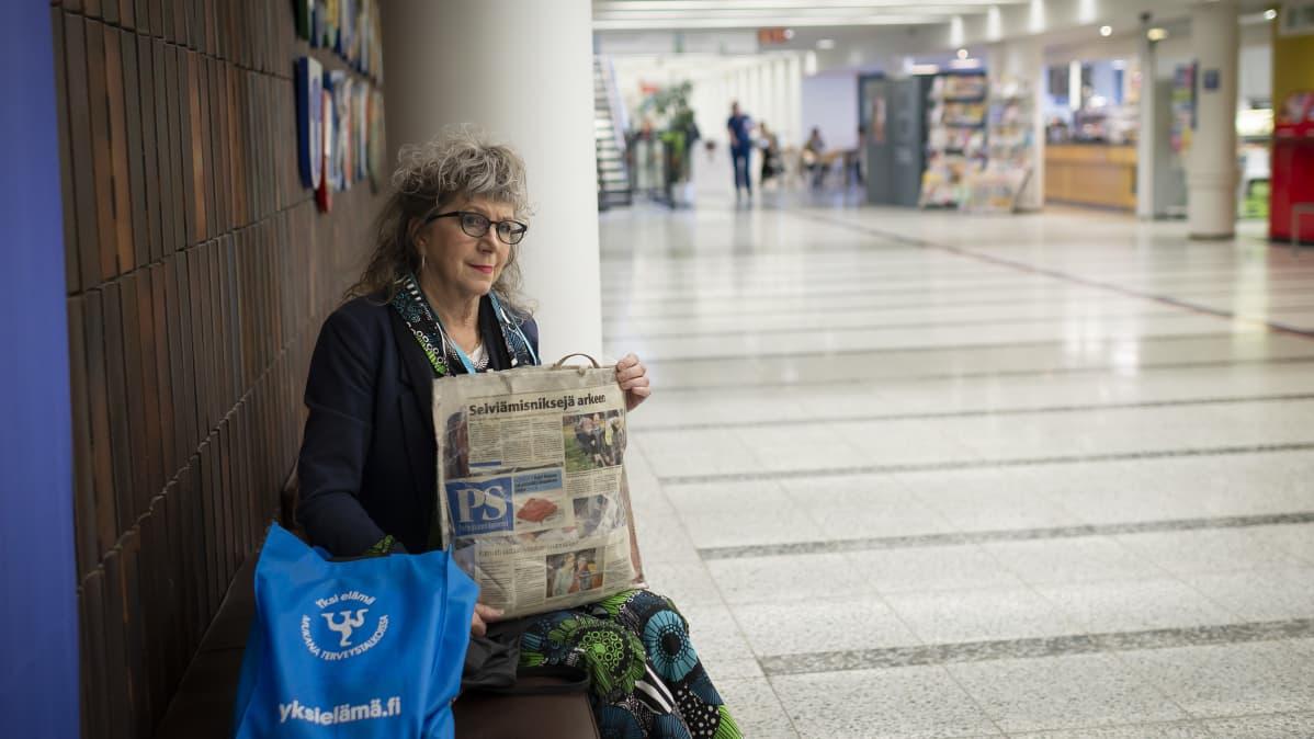 Nainen istuu kassi sylissään sairaalan pääkäytävällä.