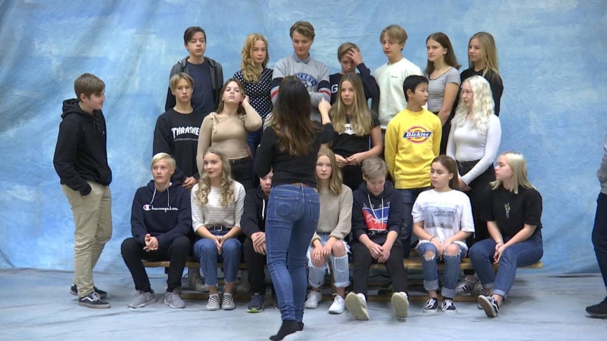 Koulukuvaaja Janina Svan (selin) järjestää Onkilahden yhtenäiskoulun 8E -luokan luokkakuvaan.
