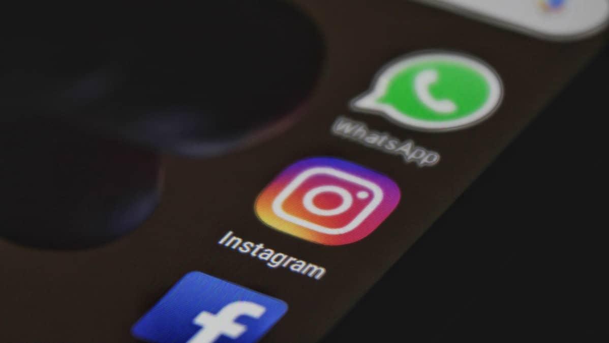 Puhelimen näytöllä näkyvät Facebookin, Instagrammin ja WhatsAppin ikonit.