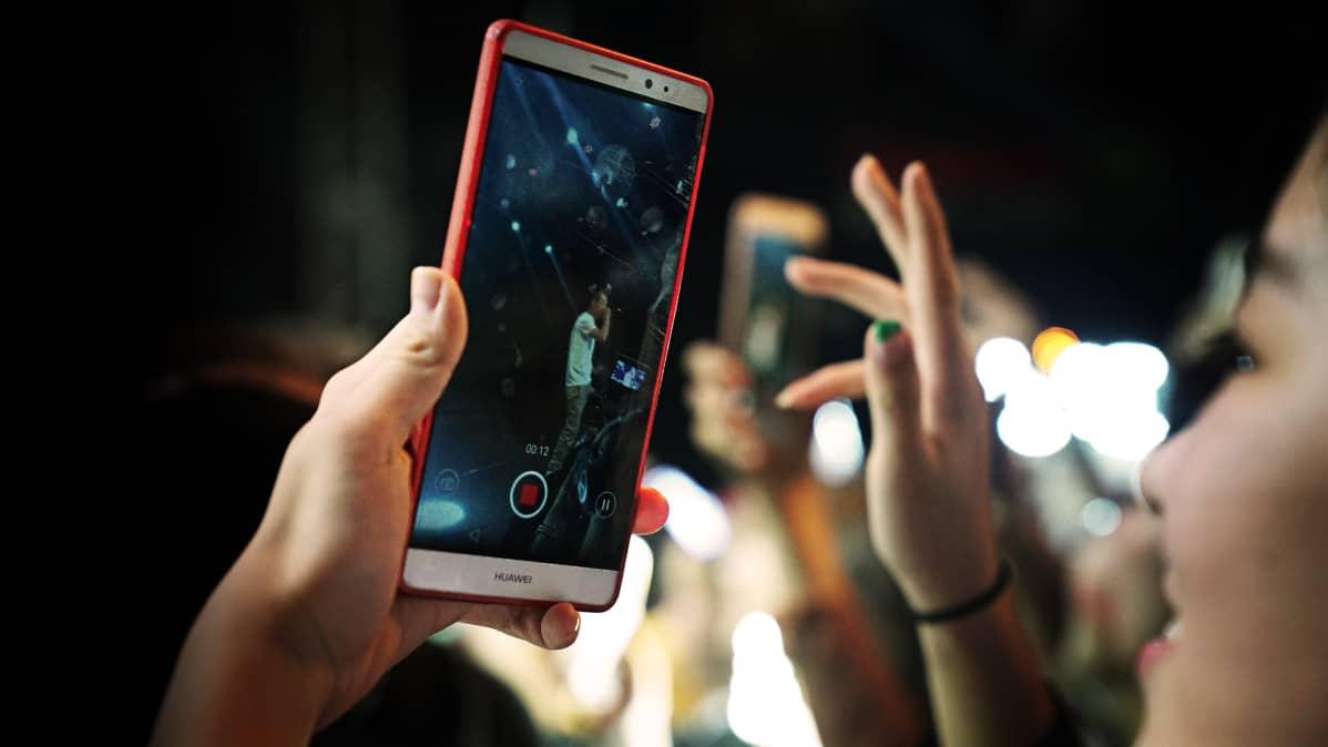 Nainen  konsertissa ja kuvaa puhelimella artistia.
