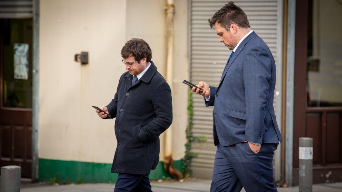 kaksi miestä kävelee kännykät kädessä