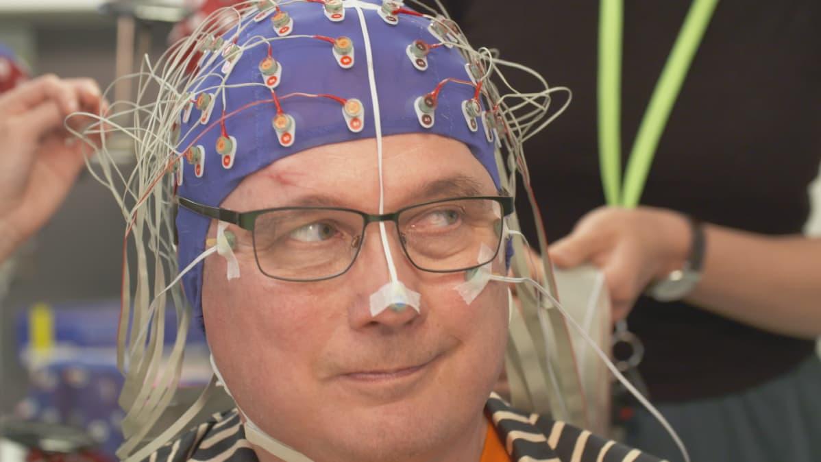 Miestä valmistellaan aivosähkökäyrän mittaukseen.