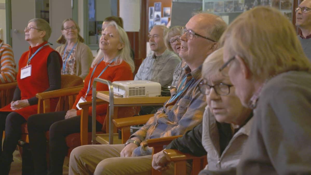 Ihmisiä istuu tuoleilla.