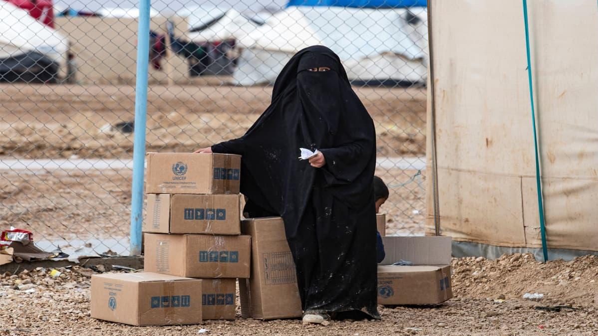 Nainen istui YK:n apupakettien vieressä al-Holin leirillä Syyriassa 9. joulukuuta.