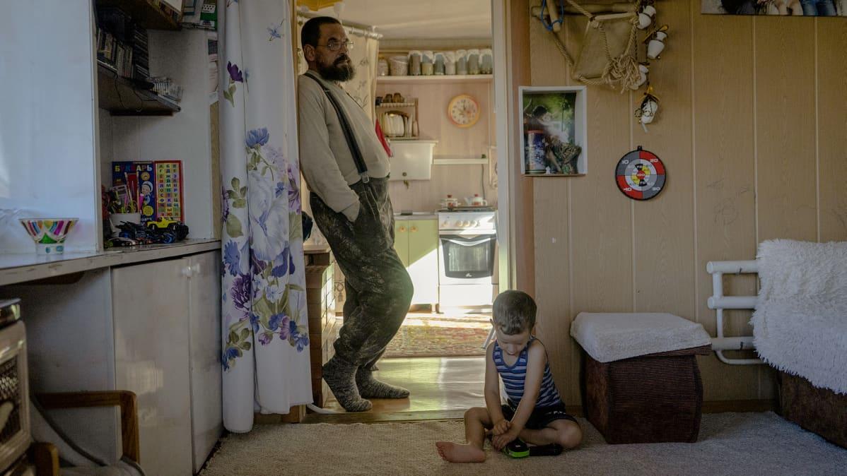 Mies seisoo huoneen ovella