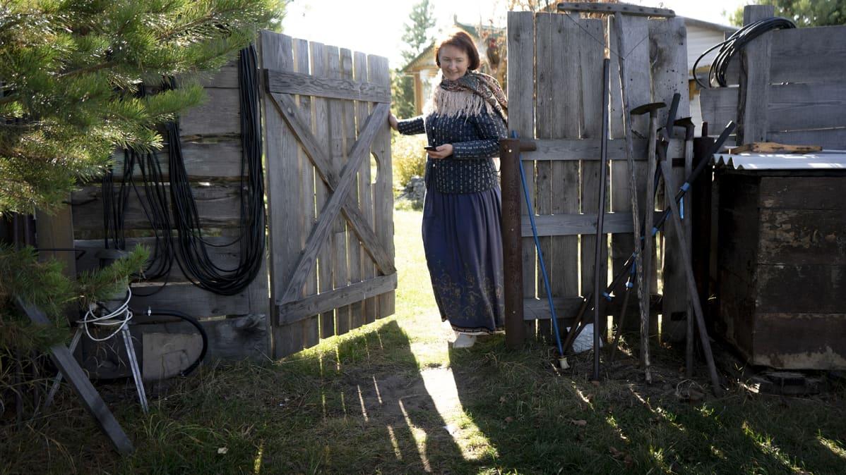Nainen avaa portin