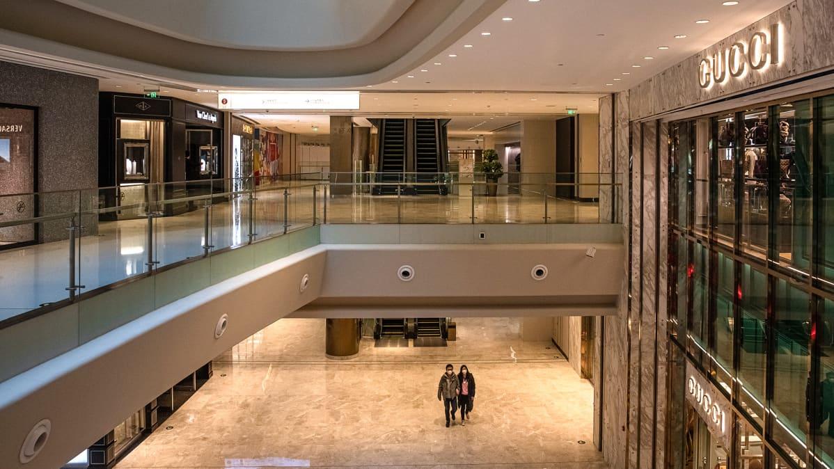 Kaksi kiinalaista kävelee tyhjässä ostoskeskuksessa Pekingissä.